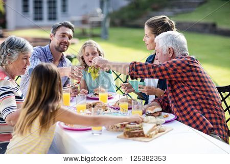 Happy family having lunch in the garden on a sunny day