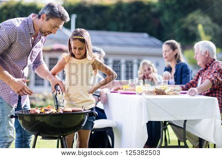 Father and daughter at barbecue grill while family having lunch in the garden