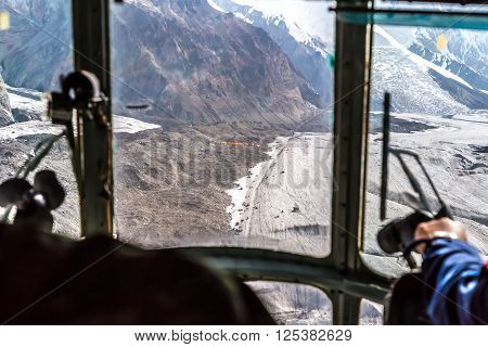 View throw Helicopter Cockpit Approaching to High Altitude Base Camp of Mountain Climbing Expedition on Massive Glacier