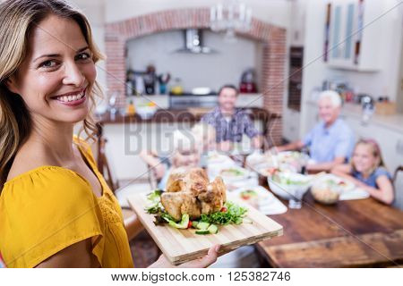 Portrait of happy woman holding a tray of roasted turkey and family dining in background