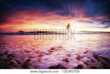 Young woman in white dress walking alone on the beach at sunset