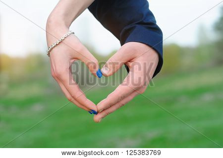 Close up of woman and man hands showing heart shape.