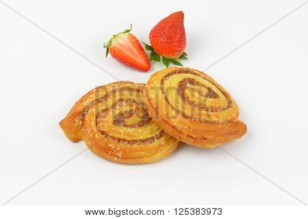 sweet cinnamon rolls and strawberries on white background