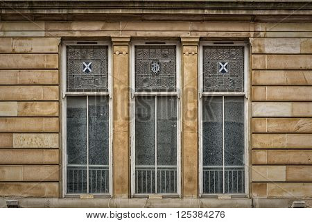 Three windows on an old tenement building in the Scottish city of Glasgow.