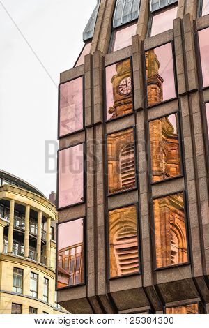 St. George's Tron Parish Church reflected onto the windows of a nearby office block in Glasgow Scotland
