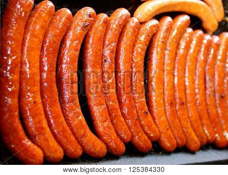 Group of sausages baking on hot iron plates. Shallow depth of field
