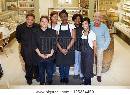 A group of deli workers standing in their shop