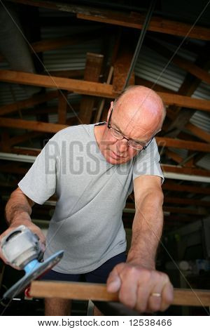 Old man sanding a wooden board