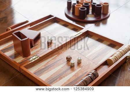 Wooden backgammon game set on wooden floor selective focus on the two white dices