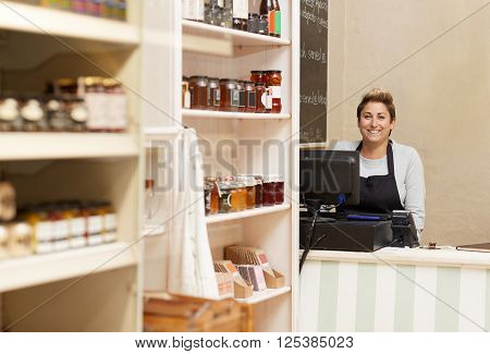 A young deli worker standing behind the counter