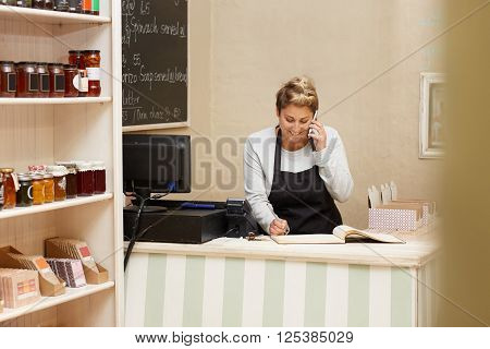 A young deli worker standing behind the counter while talking on the phone