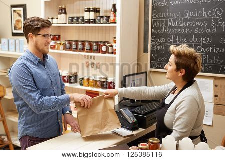 A female deli employee handing a young man a brown paper bag