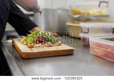 A female chef drizzling balsamic vinegar on an open sandwich