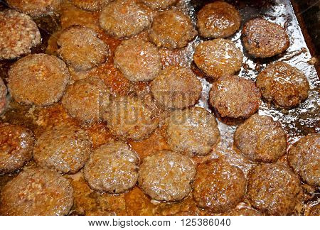 Group of juicy deer hamburgers patty baking on hot iron plate