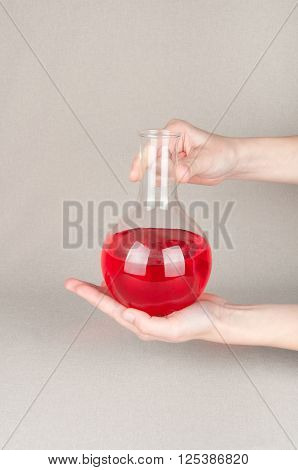 Laboratory glassware with red liquid in human's hands on white background
