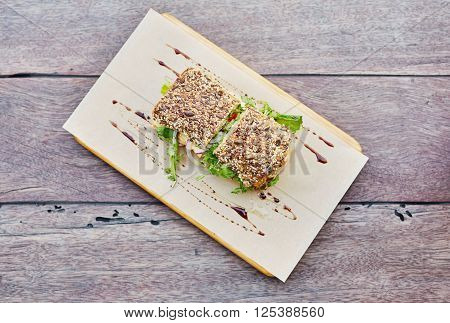 Topview of a delicious looking sandwich with whole grain bread and fresh ingredients visible presented rustically on a wooden table with balsamic vinegar sprinkled over
