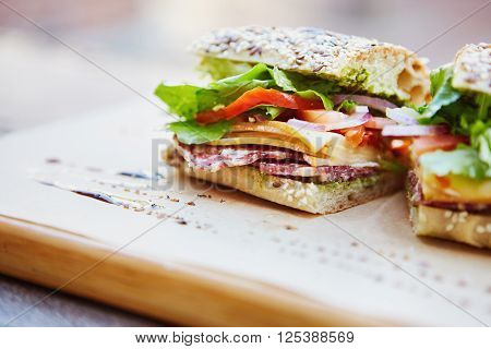 Healthy sandwich made of a fresh seeded roll, cut in half to display tasty ingredients of salami, tomato, lettuce and chees, presented on a wooden board