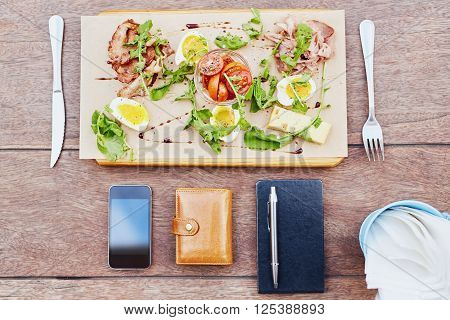 Overhead view of a fresh salad platter of meat, chees, egg and tomato with a business person's phone, diary and wallet laid on the table as well