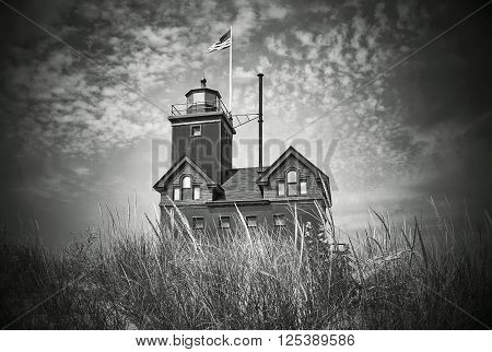 Historic Holland Michigan lighthouse in dune grass with vignette