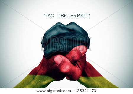 man hand patterned with the flag of Germany put together and the text tag der arbrit, labour day in German, with a slight vignette added