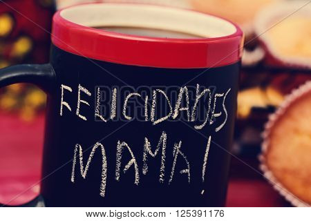 the sentence felicidades mama, congratulations mom in Spanish, handwritten with chalk in a black mug with coffee, with some muffins in the background in a set table for breakfast