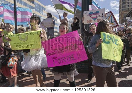 Asheville, North Carolina, USA - April 2, 2016: Colorful demonstration with enthusiastic people, creative signs, and symbolic flags to protest the new North Carolina HB2 Law that restricts the rights of those who are gay or transgender