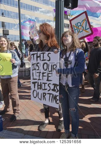 Asheville, North Carolina, USA - April 2, 2016: Crowd holds signs waves symbolic flags and protests the new North Carolina HB2 Law that restricts rights to those who are gay or transgender on April 2 2016 in downtown Ashevile NC