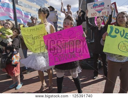 Asheville, North Carolina, USA - April 2, 2016: Crowd holds signs waves symbolic flags and protests the new North Carolina HB2 Law that restricts the rights of those who are gay or transgender