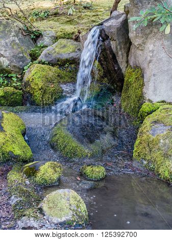 Water rushes over rocks creating a small waterfall. Location is Seattle Washington.