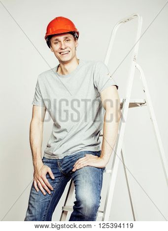 young real hard worker man isolated on white background on ladder smiling posing, business concept close up