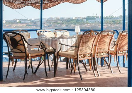 Beautifully Set Restaurant Dining Table Overlooking The Sea