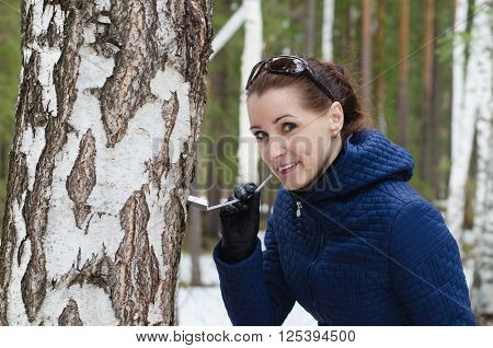 Young beautiful woman drinking birch sap in spring forest