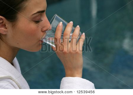 Portrait of a young woman drinking a glass of water