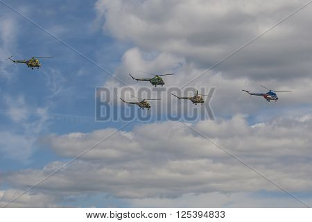 Minsk Belarus-June 21 2014: Team of MI-2 Helicopters Performing Elements in Air In Front of Spectators During Aviation Sport Event Dedicated to the 80th Anniversary of DOSAAF Foundation in Minsk on June 21 2014 in Minsk Republic of Belarus