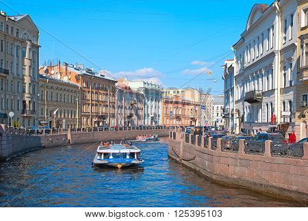 SAINT - PETERSBURG, RUSSIA - APRIL 12, 2016: Tourists in the excursion boat sail on The Moyka River along the embankments in spring time