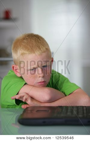Portrait of an angry little boy in front of a laptop computer