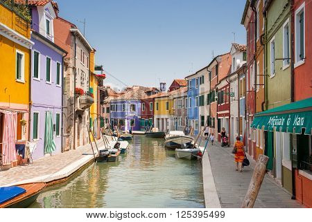BURANO ITALY - JUNE 13 2010: Colorful houses and boats at Burano island canal Italy