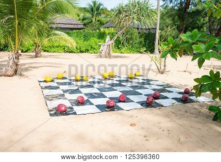 Red and yellow painted coconuts serve as checkers on a vinyl board stretched over the sand at a tropical beach resort.