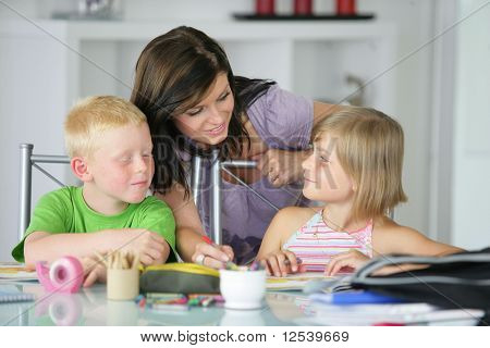 A woman helping a boy and a girl doing homework
