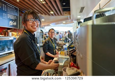 HONG KONG - MARCH 08, 2016: worker at McCafe in the Airport. McCafe is a coffee-house-style food and drink chain, owned by McDonald's.