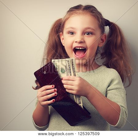 Cute happy kid girl holding wallet with much dollars with open mouth. Vintage toned closeup portrait