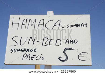 Sign announcing sun shade and sun bed in the beach of Marbella Spain