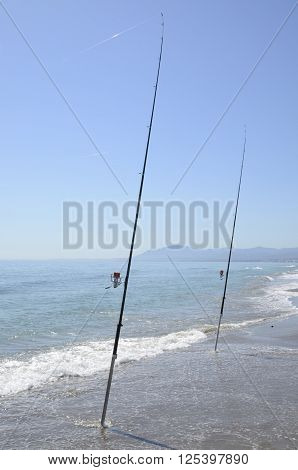 Fishing rods at the shore of the sea in Marbella Spain.