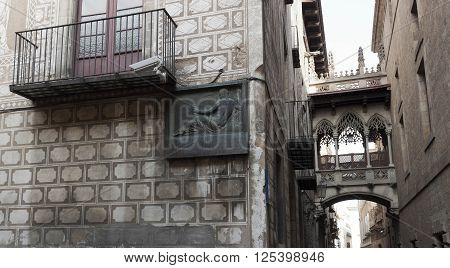 BARCELONA SPAIN - JULY 13 2013: The bas-relief on the wall in Barcelona's Gothic Quarter and the original bridge that connects the two houses located on opposite sides of the street Bizbe.