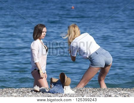 CAMYUVA KEMER TURKEY - JULY 17 2015: Photo shoot on the beach. Unidentified attractive young girls staged a photo shoot on the beach