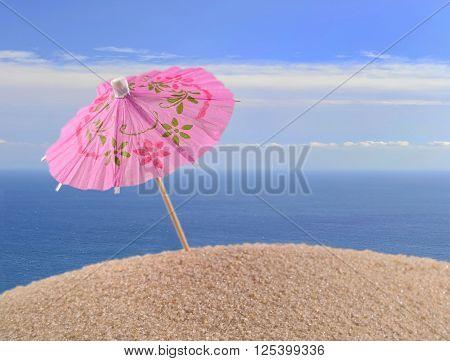 Cocktail Umbrella On A Beach Sand