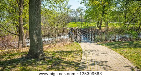 Walkway bridge in woods along the Niagara Parkway trail on a warm May spring day.  New green shoots and buds on trees and bushes.
