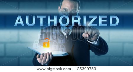 Business person is touching AUTHORIZED on a virtual interactive screen. Information technology and information security concept for access control policy and rules guarding computer resource usage.