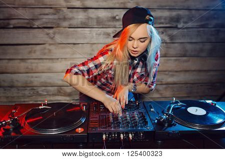 Cute dj woman having fun playing music on vinyl record deck at club party nightlife lifestyle