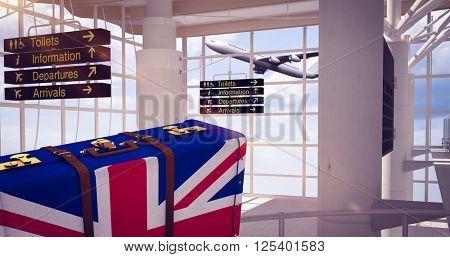 Great Britain flag suitcase against airport terminal
